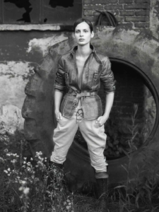 black and white location portrait of Marina against giant tire wearing leather jacket