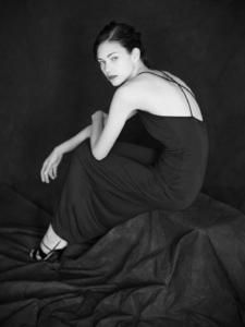 black and white sitting studio portrait of Daniela wearing a black evening dress