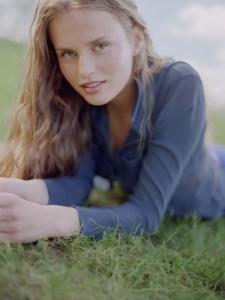 colour portrait Karolina lying on grass in a field