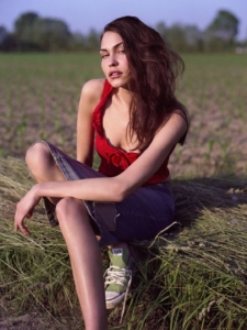 colour location portrait of Katharina sitting on straw in field