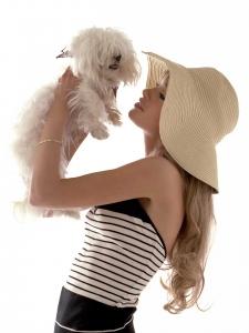 Colour high-key profile studio portrait of Eline wearing hat while holding white dog for Maxi Magazine Germany.